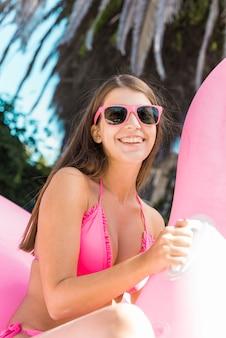 Mujer en bikini sentada en flamenco inflable rosa.