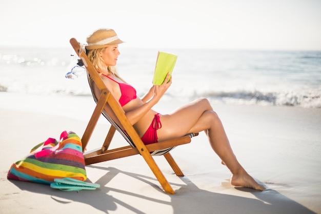 Mujer en bikini sentada en un sillón y leyendo un libro