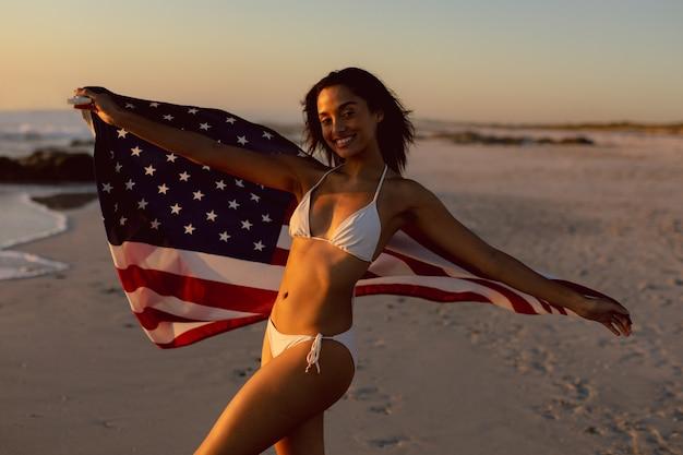 Mujer en bikini sosteniendo una bandera americana en la playa