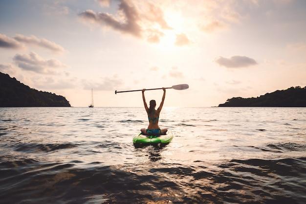 Mujer con bikini en tabla de paddle