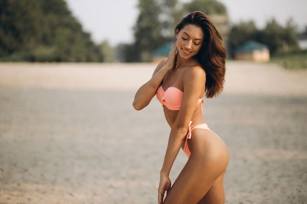 941338032bcb Mujer en traje de baño apoyándose en la columna en la playa ...