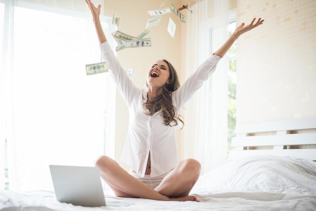 Mujer con billete de dólar en la cama