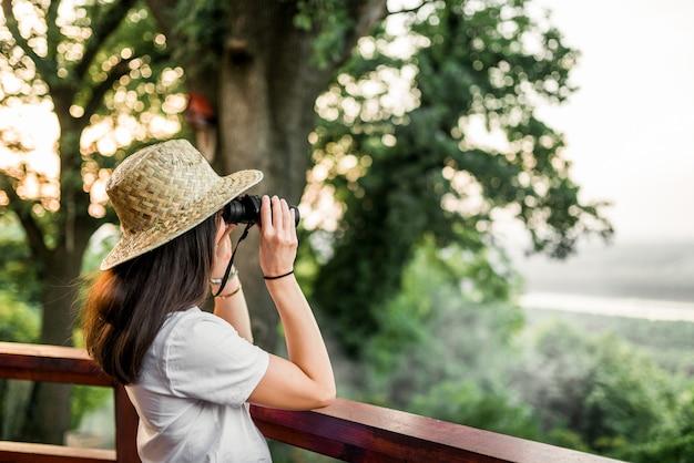 Mujer con binoculares mirando el bosque.