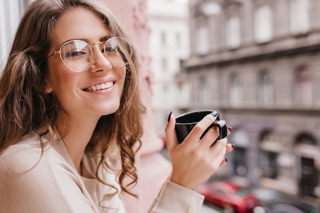 Mujer blanca emocional lleva gafas posando sobre fondo borroso con taza de bebida caliente