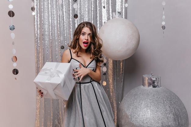 Mujer blanca emocional en vestido de fiesta largo posando con asombro, sosteniendo gran caja presente. encantadora modelo femenina en traje brillante de pie cerca de enormes juguetes navideños con regalo.