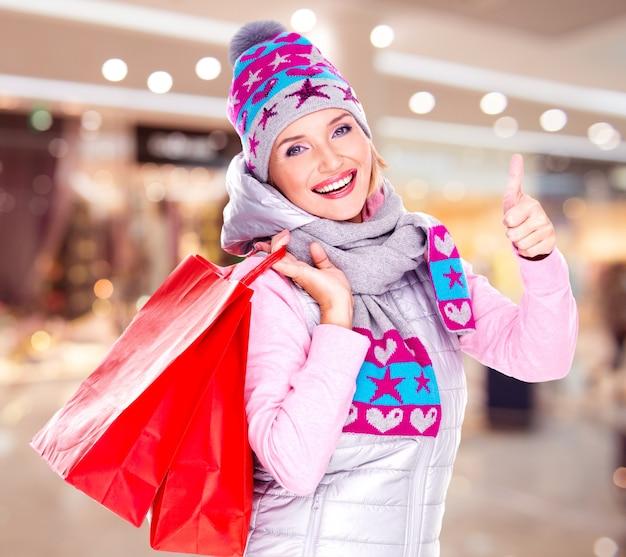 La mujer blanca feliz con regalos después de comprar