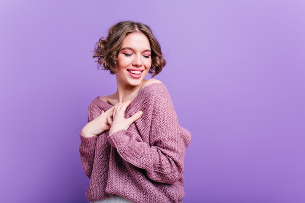 Mujer blanca inspirada viste suéter de punto suave posando con sonrisa tímida. retrato interior de una joven entusiasta con peinado de moda riendo en la pared púrpura.