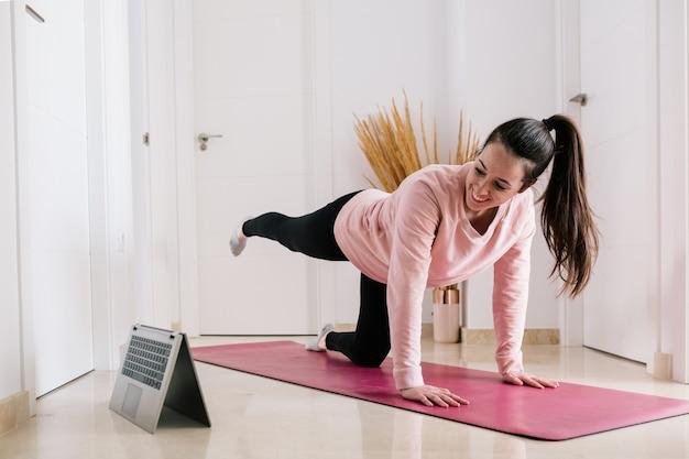 Mujer blanca de pelo oscuro entrenando en casa durante la cuarentena mientras ve la clase de deportes en la computadora portátil