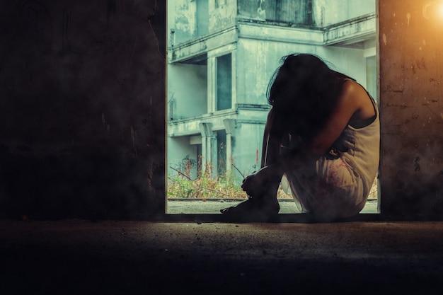 Una mujer blanca y sangrienta está sentada en la entrada de un edificio abandonado.