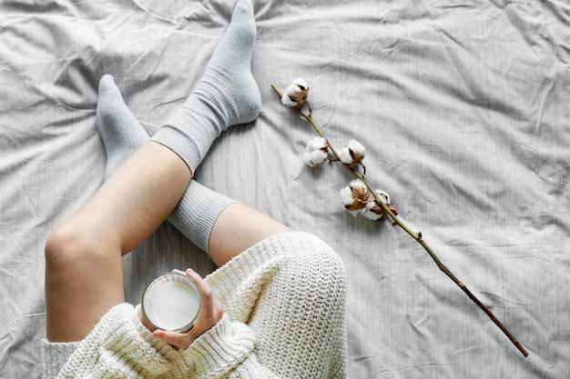 Mujer blanca sentada en la cama con leche caliente en invierno