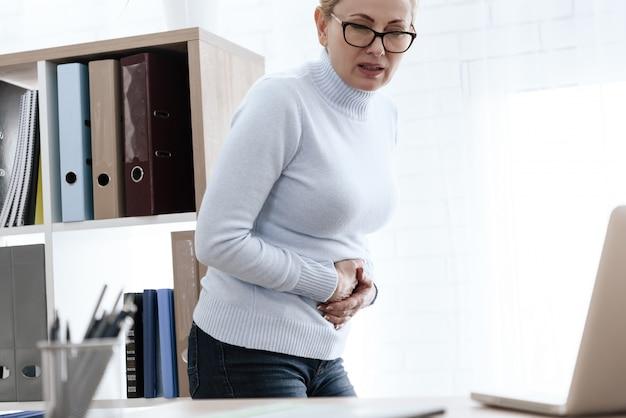Una mujer blanca tiene dolor de estómago en el trabajo.