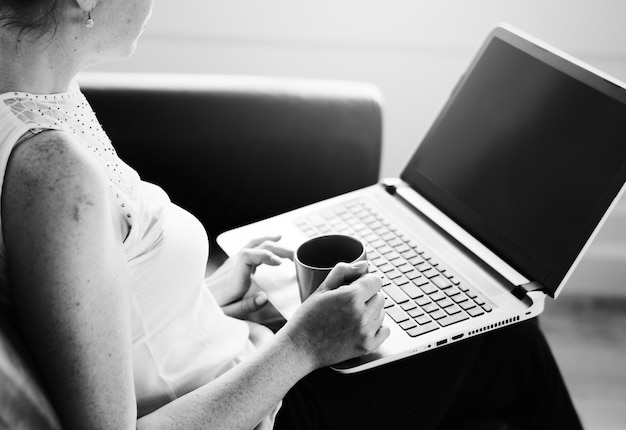 Mujer blanca, usar la computadora portátil, en, sofá