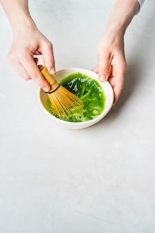 La mujer de blanco prepara el té verde japonés matcha batiéndolo en un tazón