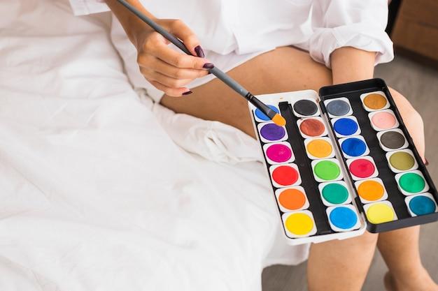 Mujer en blanco sentado con pinturas de acuarela en manos