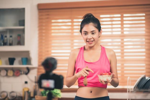 Mujer blogger asiática que hace vlog cómo adelgazar y adelgazar, mujer joven que usa una cámara de grabación