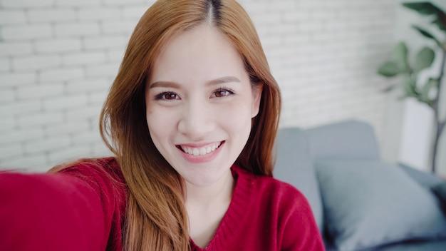 Mujer blogger asiática que usa un teléfono inteligente para grabar video vlog en la sala de estar en casa