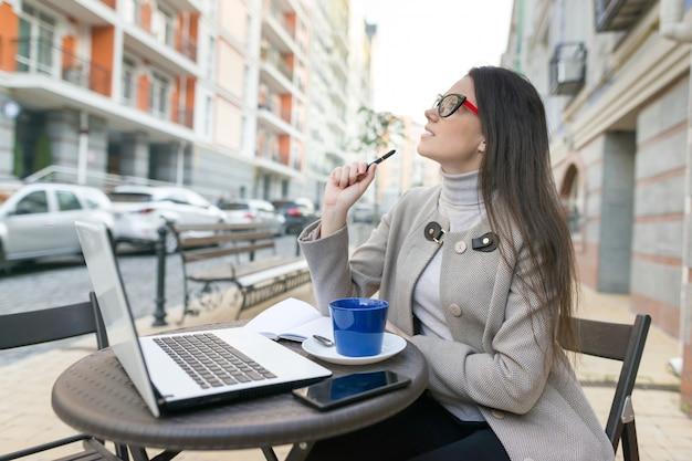 Mujer blogger freelance en café al aire libre con computadora