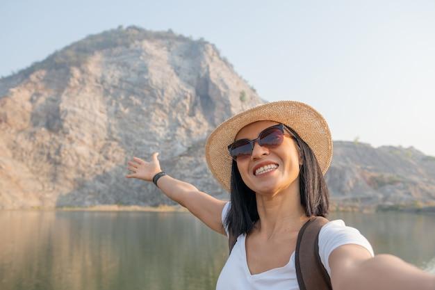 Mujer blogger mochilero asiático con smartphone tomando selfie