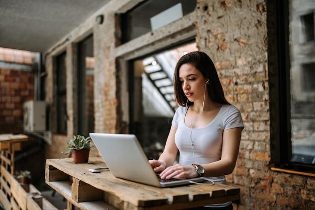 Mujer blogger usando laptop y usando auriculares.