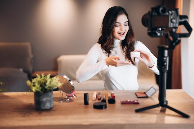 Mujer bloguera de belleza filmando tutorial de rutina de maquillaje diario en cámara. influencer linda mujer transmisión en vivo revisión de productos cosméticos en estudio casero. trabajo de vlogger.