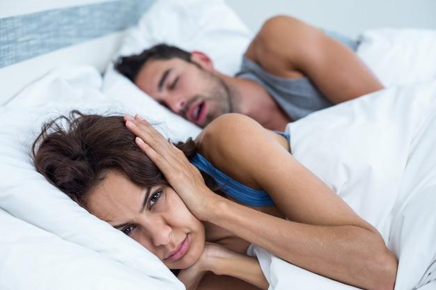 Mujer bloqueando las orejas con las manos mientras el hombre roncando en la cama