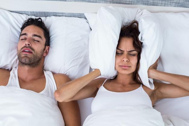 Mujer bloqueando las orejas mientras el hombre roncando en la cama