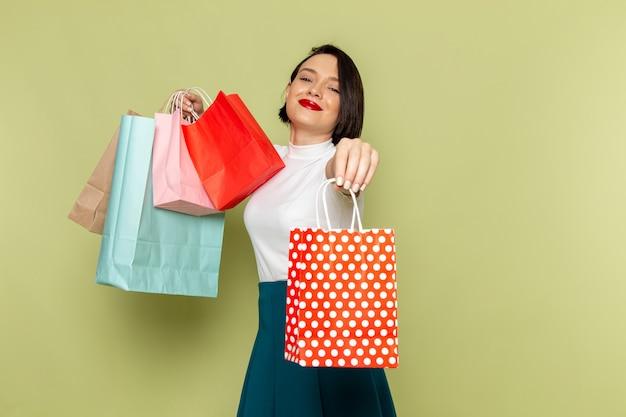 Mujer con blusa blanca y falda verde sosteniendo paquetes de compras