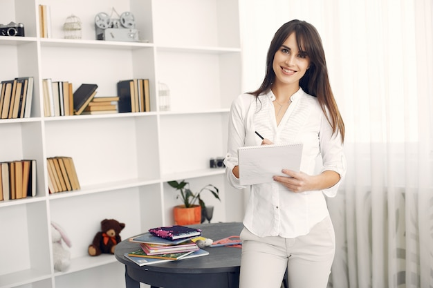Mujer en una blusa blanca de pie con libros