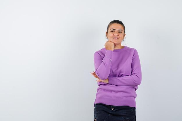 Mujer en blusa de lana apoyando la barbilla en la mano y luciendo sensato