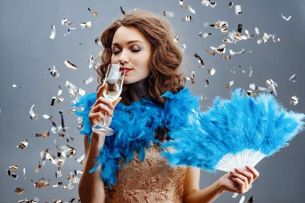 Mujer en una boa azul está de pie en el estudio con un abanico de plumas en la mano y bebiendo champán.