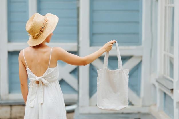 Mujer con bolsa de algodón junto a la pared azul. maqueta de diseño. bolsa ecológica reutilizable para compras. concepto de desperdicio cero.