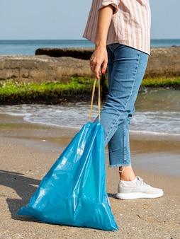 Mujer con bolsa de basura con botella de plástico reciclable