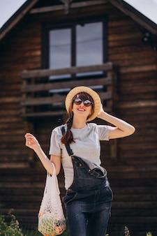 Mujer con bolsa ecológica con fruta en un campo