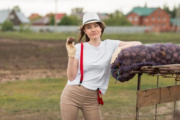 Mujer con una bolsa de frutos en una granja