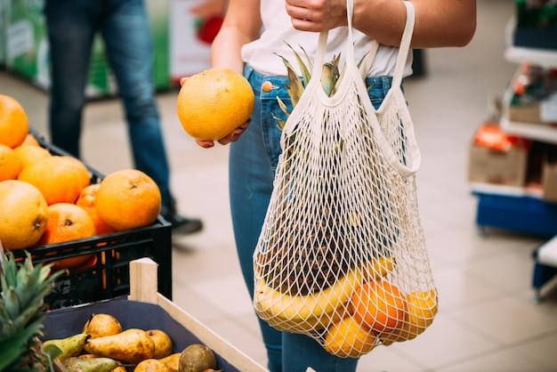 Mujer con bolsa de malla llena de verduras frescas comprando en la tienda, cero concepto de residuos