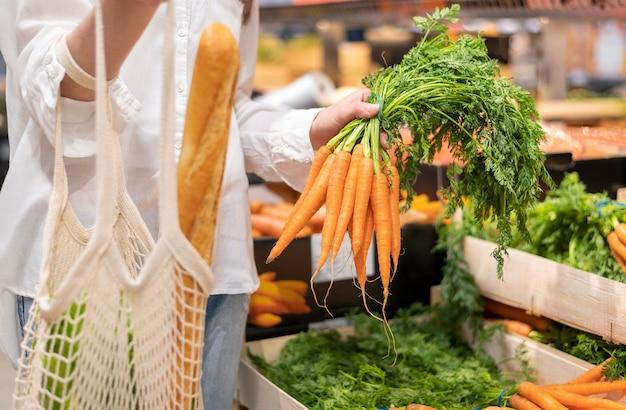 Mujer con bolsa reutilizable y zanahorias en la tienda de comestibles