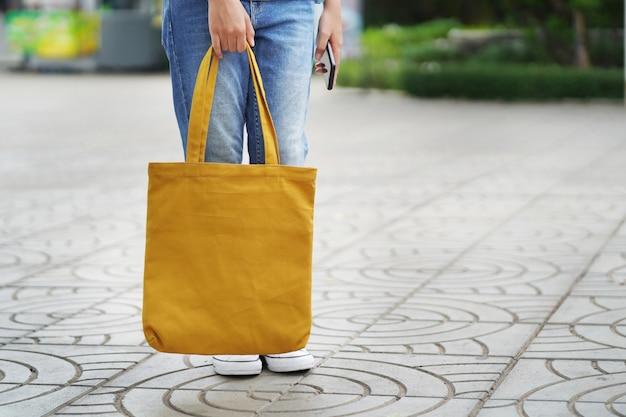 Mujer con bolsa de tela para compras en grandes almacenes.