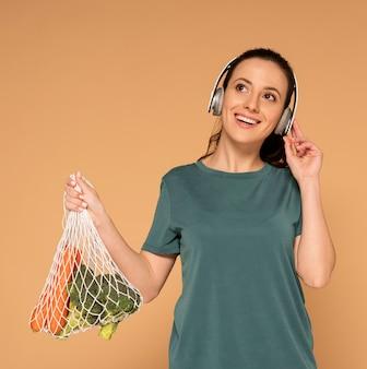 Mujer con bolsa de tortuga y auriculares
