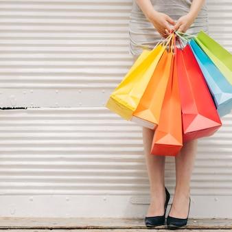Mujer con bolsas de colores en la pared