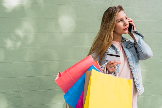 Mujer con bolsas de compra y tarjeta de crédito hablando por teléfono