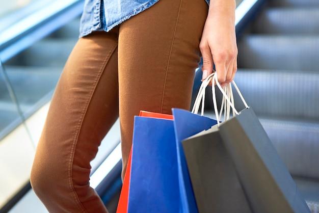 Mujer, con, bolsas de compras, en, centro comercial