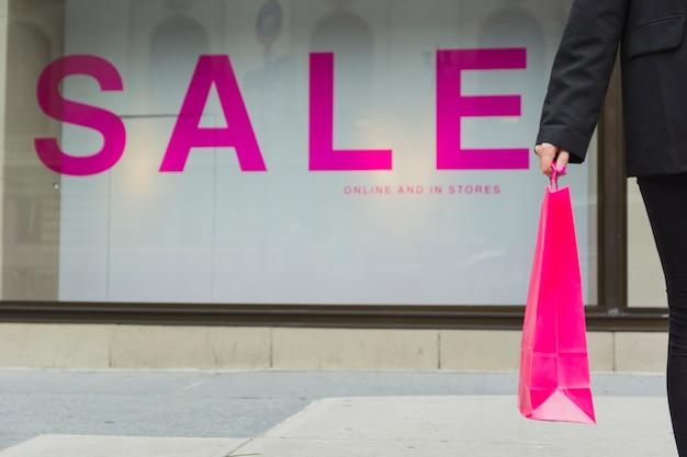 Mujer con bolsas de compras cerca de letras de venta