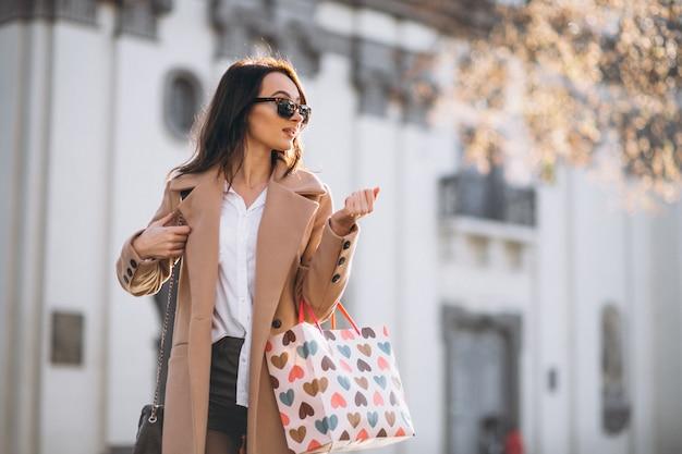 Mujer con bolsas de compras fuera de la calle.