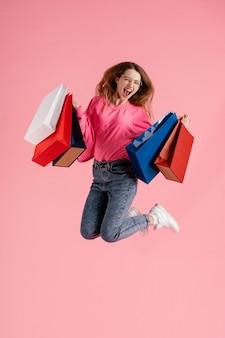 Mujer, con, bolsas de compras, saltar
