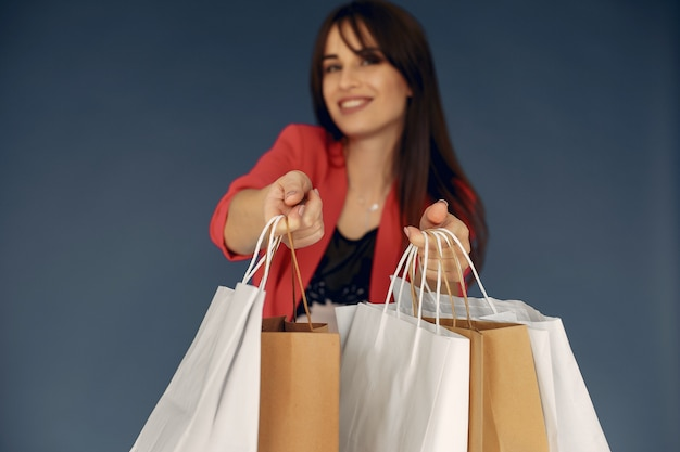 Mujer con bolsas de compras sobre un fondo azul