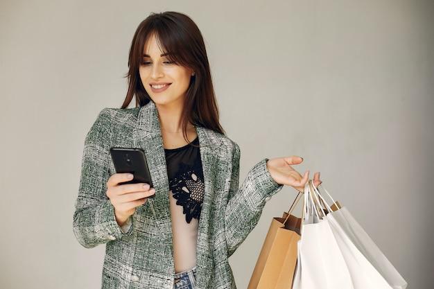 Mujer con bolsas de compras sobre un fondo blanco.