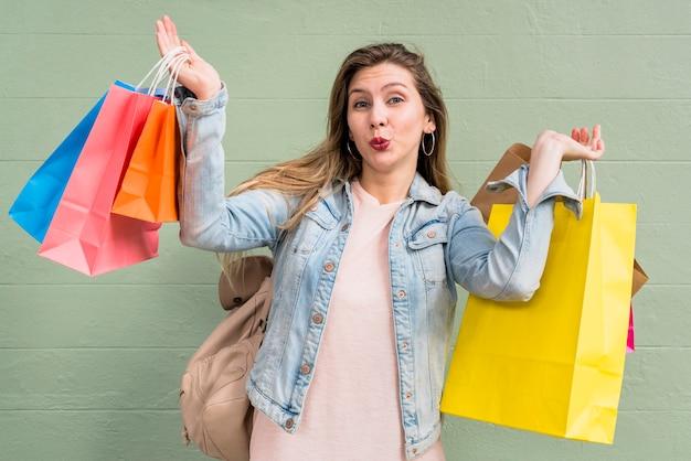 Mujer, con, bolsas de compras, soplar beso