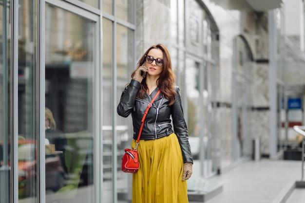 Mujer con bolso rojo caminando mientras habla por teléfono cerca de un edificio comercial