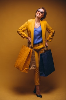 Mujer con los bolsos de compras en estudio en el fondo amarillo aislado