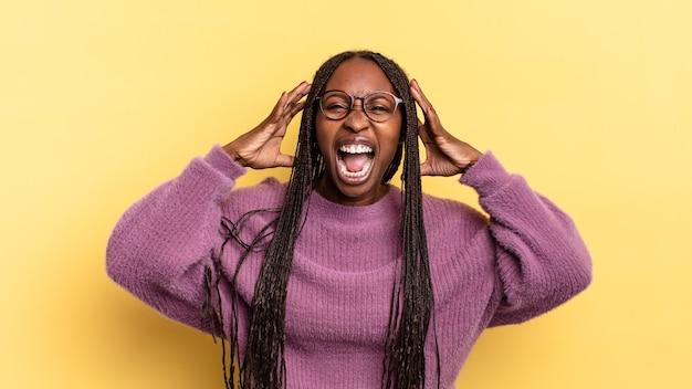 Mujer bonita afro negra gritando de pánico o ira, conmocionada, aterrorizada o furiosa, con las manos al lado de la cabeza